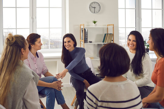 Happy positive smiling female coach, therapist or business team manager supporting and motivating young women in group therapy session or corporate staff training meeting at work
