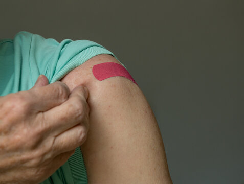 Senior caucasian man holding up shirt sleeve to show the bandaid after coronavirus vaccine shot in the shoulder