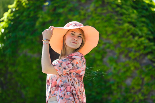 A charming girl in a light summer sundress and a pareo hat is walking in a green park. Enjoys warm sunny summer days