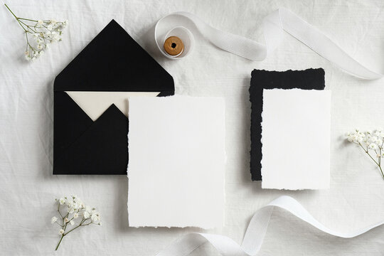 Wedding invitations mockups and black envelopes on textile background with flowers and white ribbon. Elegant wedding flat lay composition. Top view.