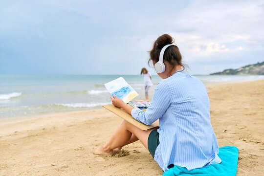 Relaxation on sea, mature woman in headphones with watercolors painting