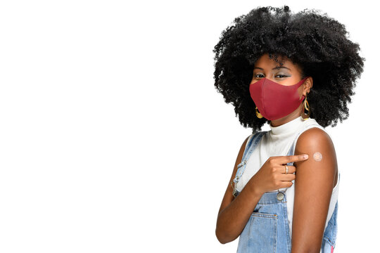 black teenager wearing protective mask against covid-19 with a smile on his face shows the vaccine brand covid-19 isolated on white background