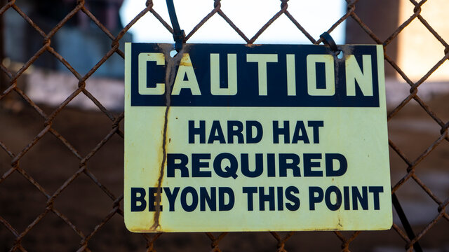 Worn out hard hat warning sign