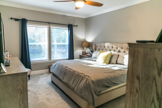 Spacious beige carpeted master bedroom with king sized bed