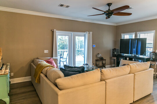 Small living room with a cream colored couch and a television and a fan.