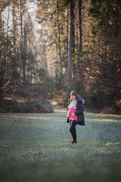 Pregnant young woman standing in the middle of beautiful forest meadow