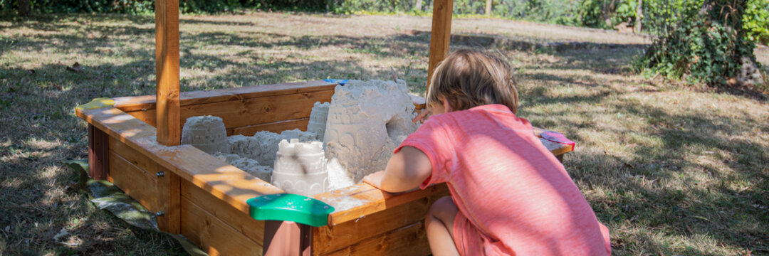 Toddler child playing with sand building castle