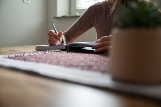Woman, student, writing with pencil in notepad