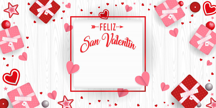 FELIZ SAN VALENTIN - Happy Valentine's Day in Spanish language - in a square frame surrounded by gift boxes, hearts, stars and red and pink balls on white wooden background. Vector image