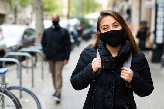Portrait of young woman wearing face mask for disease protection walking outside at cold day