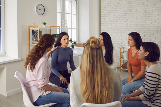 Angry young woman telling shocking story in therapy session or support group meeting. Female friends talk, share bad news, discuss life situations, give advice and help each other cope with problems