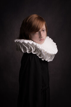Classic renaissance portrait of red headed boy in black wearing a large white collar like in the oldmasters paintings