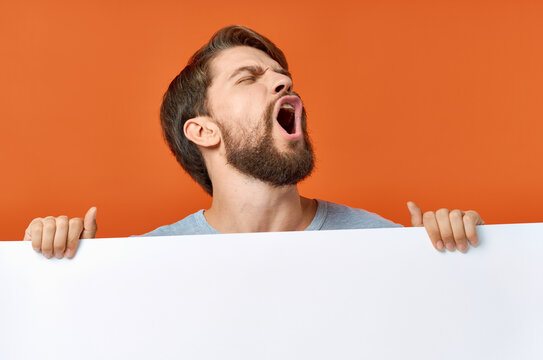 emotional man peeking out from behind a poster on an orange background Copy Space mockup