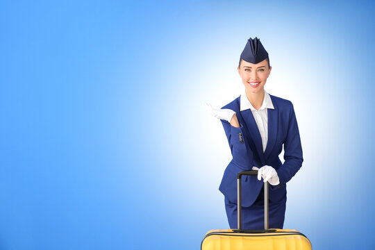 Beautiful stewardess with suitcase on color background