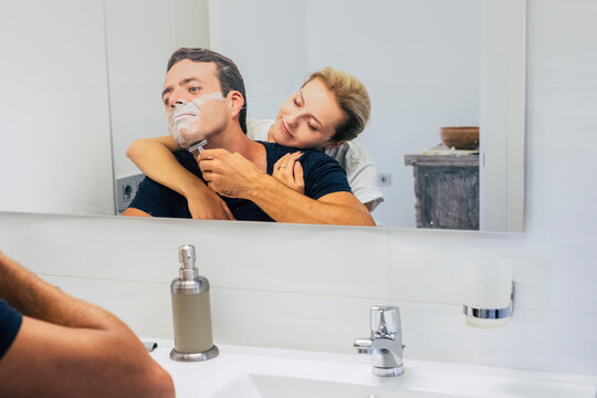 Young couple at home in the bedroom while man do and cut beard ready to start the day - love people indoor leisure activity - girlfriend hug boyfriend from back and enjoy