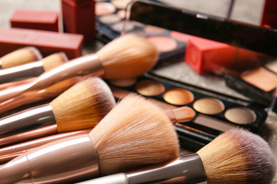 Set of makeup brushes with cosmetics on table, closeup