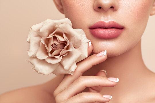 Beautiful model with a rose. Perfect woman face makeup close up. Lipstick. Beautiful nails