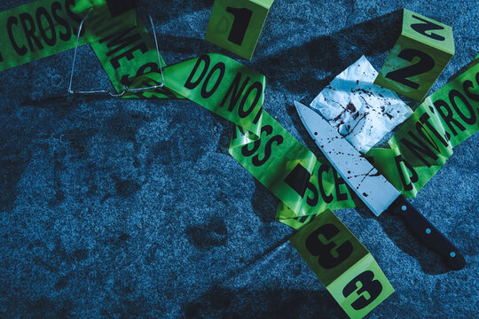 Flat lay composition with evidences and crime scene markers on stone background at night