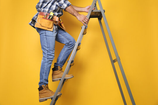 Professional builder climbing up metal ladder on yellow background, closeup