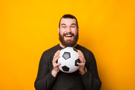 Portrait of happy bearded man holding soccer ball over yellow background.
