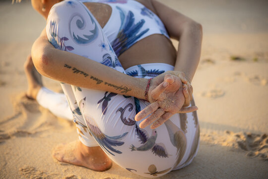 Beach yoga. Close up of Marichyasana I, forward extension. Hand in gyan mudra. Stretching exercise. View from back. Yoga retreat in Bali. Copy space.