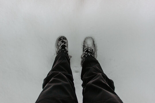 Detail of warm waterproof boots in deep fresh snow.Female feet in black shoes, winter walking in snow.High angle view of standing female legs with snowy boots. Winter scenic background copy space.