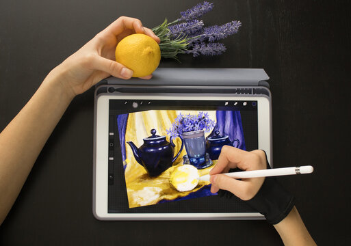 A girl in a special glove draws a still life picture with a pencil on an electronic tablet. The concept of inspiration, creativity, self-development, hobby, art