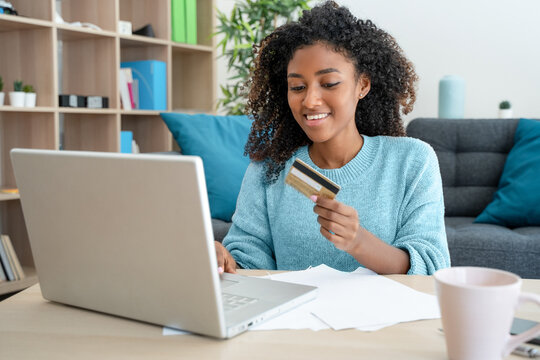 African american woman shopping online through laptop using credit card at home.