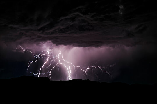 Powerful lightning storm in the American Southwest. One sees the silhouette of the hills on bottom, the lightning, and the cumulonimbus clouds.
