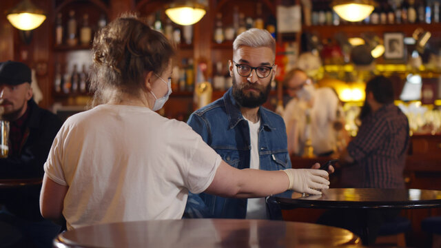 Waitress wearing safety mask and gloves taking empty glasses from tables in modern bar