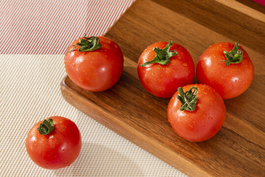 Top view of delicious wet tomatoes on a wooden board