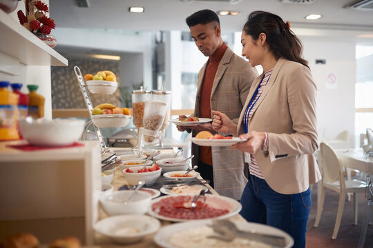 young asian female talking with afro-american male, choosing food at lunch break buffet