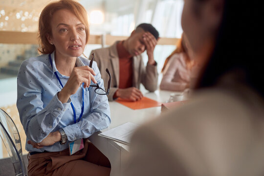 female boss talking to a colleague with attention, holding glasses