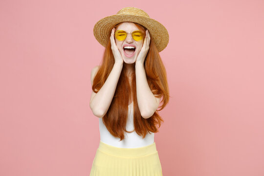 Young irritated nervous redhead woman ginger long hair wear straw hat glasses summer clothes holding face with hands shouting screaming closed eyes isolated on pastel pink background studio portrait.