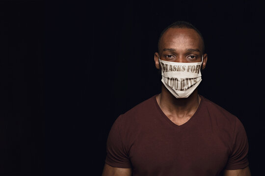 Man wearing protective face mask with sign masks for 100 days in USA, America. Copyspace, black background. Coronavirus pandemic, prevention spreading, lockdown, medicine and healthcare concept.
