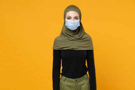 Young arabian muslim woman in hijab green clothes sterile face mask safe from coronavirus virus covid-19 during pandemic quarantine isolated on yellow background. People religious lifestyle concept.