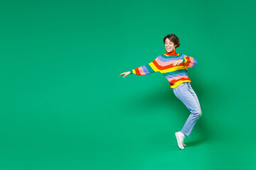Full length side view of cheerful funny young brunette woman 20s in basic casual colorful sweater dancing standing on toes spreading hands isolated on bright green color background studio portrait.