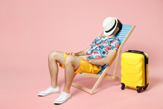 Full length of young traveler tourist man in summer clothes sit on deck chair covering face with hat isolated on pink background. Passenger traveling abroad on weekend. Air flight journey concept.