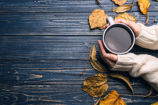 Woman with cup of hot drink at blue wooden table, top view with space for text. Cozy autumn atmosphere