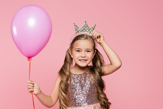 joyful little girl in dress adjusting crown and holding balloon isolated on pink