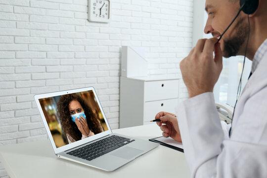 Hotline service. Doctor consulting patient online via laptop indoors