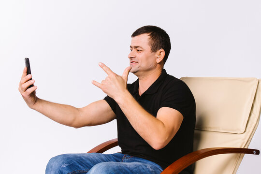 A man sitting in a leather armchair communicates non-verbally via video communication, showing I Love You to his soulmate. White background.