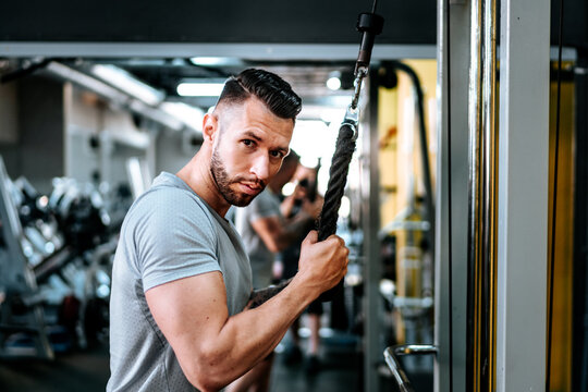 bodybuilding details and fitness workout. Man in sport gear working out at gym. Close up portrait.