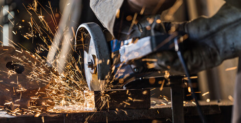 Fototapeta grinding cutting metal sheet with angle grinder machine and sparks, Close up. obraz