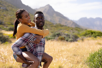 Fit african american couple resting and embracing in mountain countryside