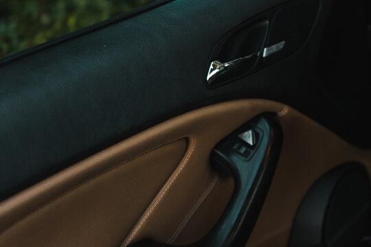 Selective focus shot of a car's interior: door handle and door lock controls