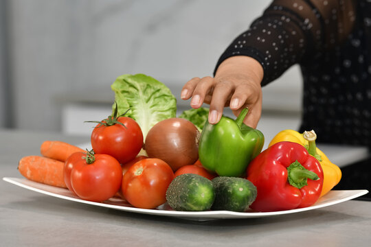 A female's hand taking a green bell pepper from a plate with fresh vegetables