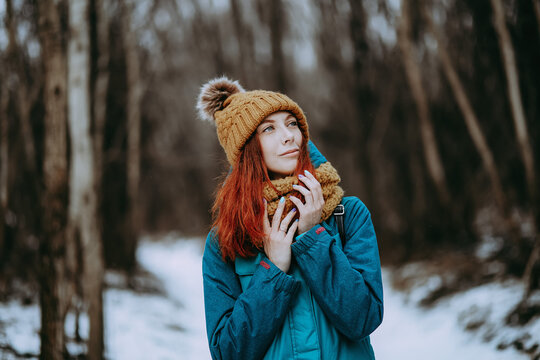 Aesthetic winter portrait with pretty redheaded girl. Cute russian model with long red hair and winter dress walking in dark forest