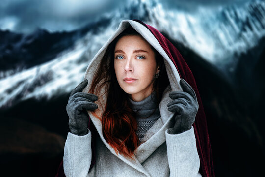 Beautiful close-up portrait of a redheaded girl. Gorgeous trendy young woman with luxurious long red hair poses against a backdrop of blurry snow-covered mountains.