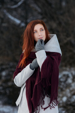 Sniling redheaded woman on winter walk. Outdoor portrait with beautiful ginger model in dark finter forest